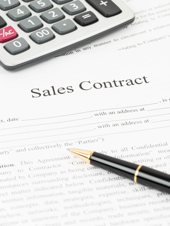 Sales contract document with calculator and pen