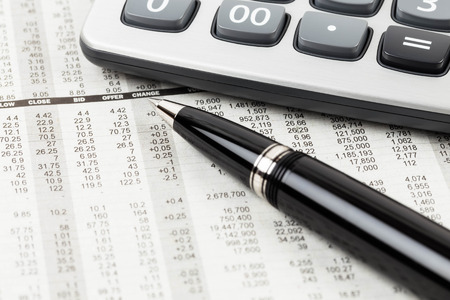 Pen and calculator rest on stock price detail financial newspaper
