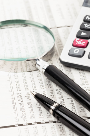 wallstreet: Pen, calculator, and magnifier rest on stock price detail financial newspaper