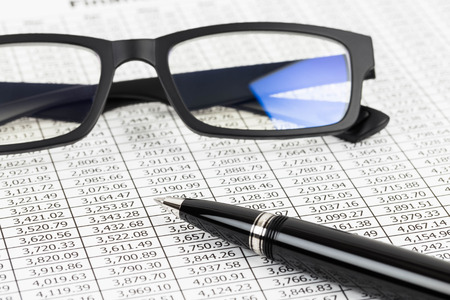 brand monitoring: Finance report analysis with pen, and glasses Stock Photo