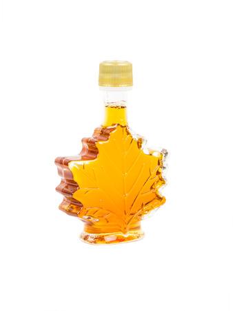 in syrup: Hoja botella de jarabe de arce forma en el fondo blanco