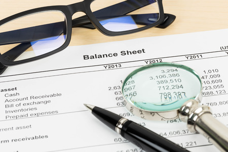 Balance sheet financial report with pen, magnifier, and glasses