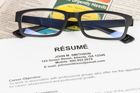 classify: Resume and glasses on classify newspaper concept job applying Stock Photo