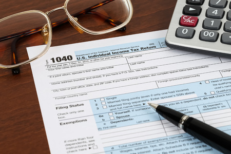taxation: Tax form with pen, glasses, and calculator taxation concept