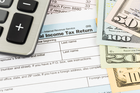 federal tax return: Tax form with calculator and banknote taxation concept Stock Photo