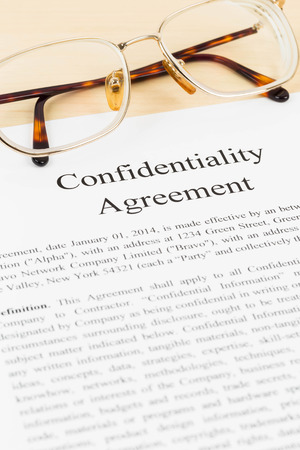 confidentiality: Confidentiality agreement document with glasses close-up