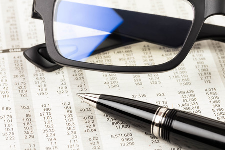 stock investing: Pen and glasses rest on stock price detail financial newspaper