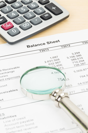 Balance sheet financial report with magnifier, and calculator