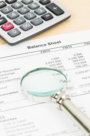 Bilan de rapport financier avec loupe, et une calculatrice Banque d'images - 36419911
