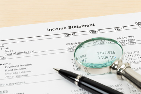 statement: Income statement with pen, and magnifier; statement is mock-up