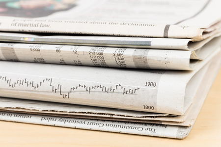 Stack of business newspapers on table Stock Photo