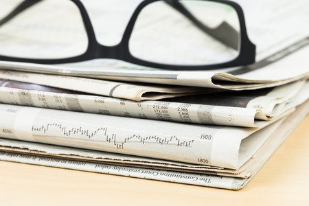 newsprint: Stack of business newspapers on table with glasses