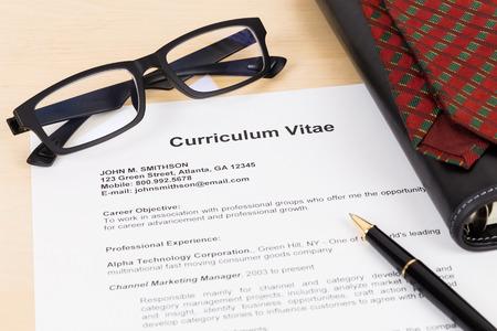 Curriculum vitae with pen, glasses, organizer, and neck tie; CV is mock-up Standard-Bild