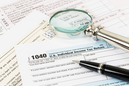 Tax form with pen and magnifying glass taxation concept