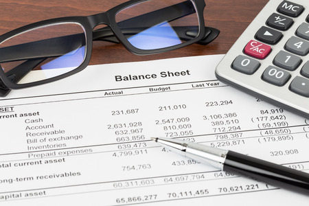Balance sheet financial report with pen, glasses, and calculator; document is mock-up