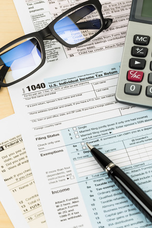 Tax form with glasses, calculator, and pen