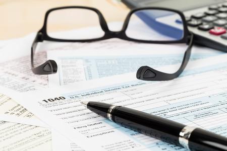 ingresos: Formulario de impuestos con gafas y calculadora de enfoque en la pluma