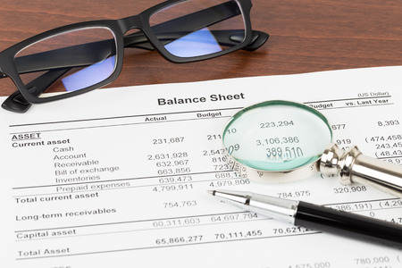 Balance sheet financial report with glasses, and magnifier; document is mock-up