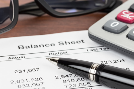Balance sheet financial report focus at pen; document is mock-up