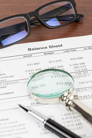 Balance sheet financial report with pen, glasses, and magnifier; document is mock-up