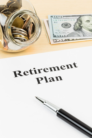 Retirement plan with banknote, coin jar, and pen photo