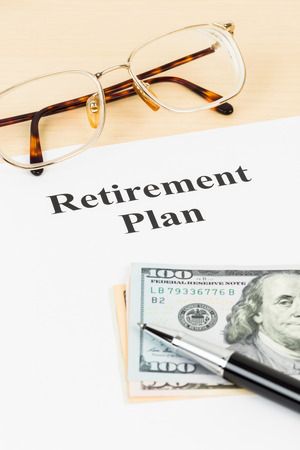 Retirement plan with banknote, glasses, and pen
