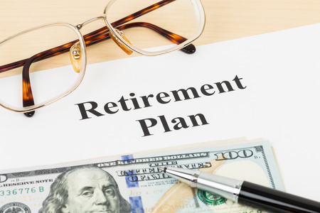 Retirement plan with banknote, glasses, and pen photo