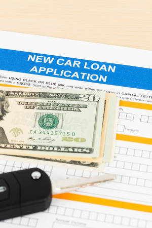 car loan: Car loan application with car key and dollar banknote; document is mock-up