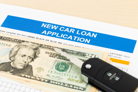Car loan application with car key and dollar banknote; document is mock-up