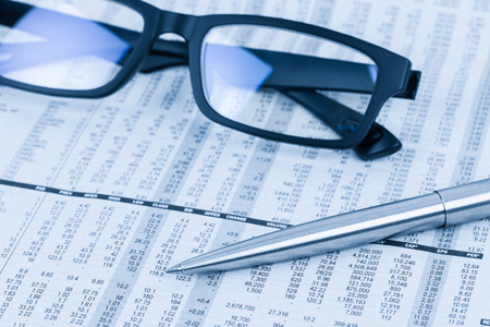stock price: Pen and glasses rest on stock price detail financial newspaper