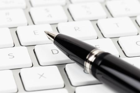 Pen on keyboard concept blog writer