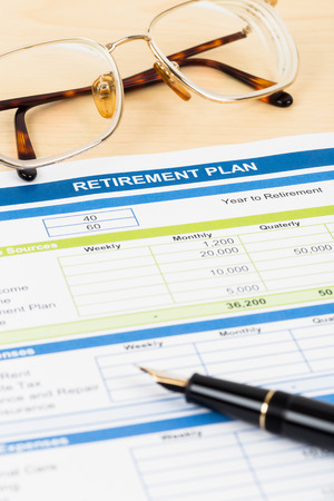Retirement plan with glasses and pen document is mockup photo