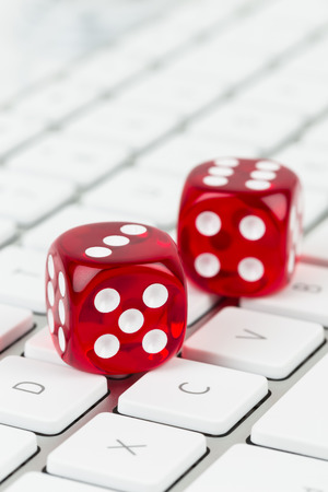 red dice: Three red dice on keyboard online casino concept