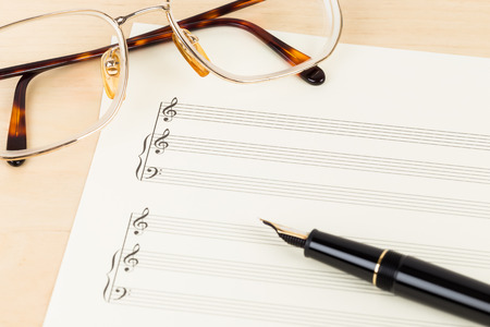 partition musique: Partition Blank sur papier de couleur cr�me avec des lunettes et un stylo Banque d'images