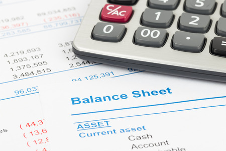 Balance sheet report with calculator; document is mock-up 版權商用圖片