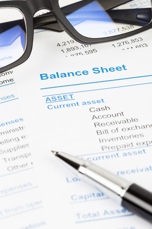 sheet: Balance sheet report with glasses; balance sheet is mock-up Stock Photo