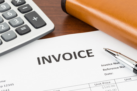 Invoice with pen, calculator, and organizer; document is mock-up