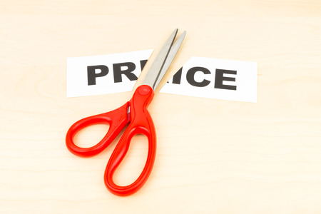 cut price: Price in paper cut by scissor on wooden desk concept price cut