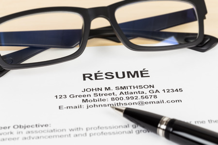 Resume with pen and glasses; resume is mock-up