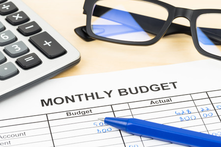 Home budget planning sheet with pen, glasses, and calculator