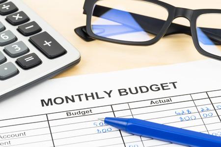 Thuis budget planning blad met pen, glazen en rekenmachine