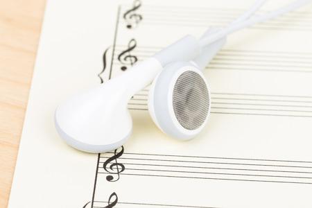 partition musique: Écouteurs sur la couleur de la crème partition de papier Banque d'images