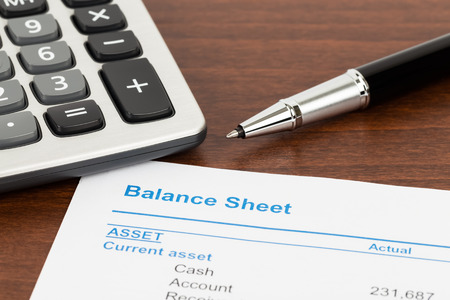 Balance sheet report with calculator and pen; document is mock-up Stock Photo