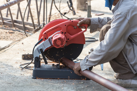 craftman: A craftman is cutting steel outdoor with a machine