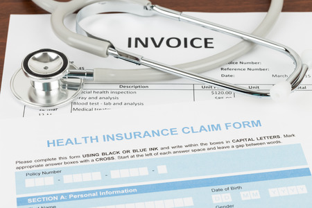 Ziektekostenverzekering aanvraagformulier en de factuur met een stethoscoop; factuur en vorm zijn mock-up Stockfoto
