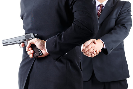 betray: Businessman hiding gun while handshaking concpet for dishonesty Stock Photo