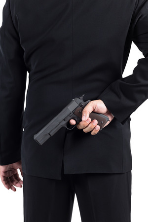 unethical: Businessman hiding gun concept for dishonesty