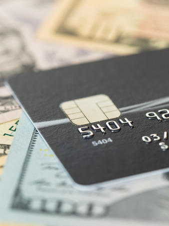 Black credit card on dollar banknote