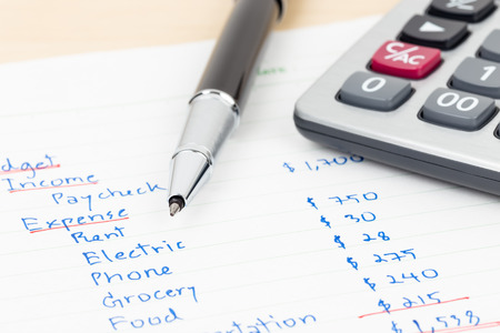 efectivo: Presupuesto casero Escritura de la mano con la calculadora Foto de archivo