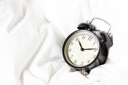 white blanket: Alarm clock on white blanket